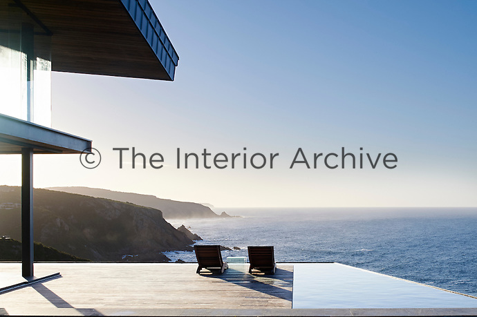 Its panoramic views overlook the cliffs, local stone and timber exterior, and sliding glass panels all enhance the natural palette of sea, sky and shrubbery.<br /> <br /> There is no division between indoor and out on a windless day when the frameless glass stacking doors are open. <br /> <br /> The house is dramatic, but when you are inside it, a lot of it disappears. The roof is so high you lose the roof and all you experience is the view and the landscape.