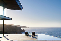 Its panoramic views overlook the cliffs, local stone and timber exterior, and sliding glass panels all enhance the natural palette of sea, sky and shrubbery.<br />