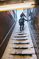 Riders ascend snow covered steps to leave the 23rd Street IND station in New York during Winter Storm Jonas on Saturday, January 23, 2016. Due to blizzard conditions the MTA announced they will be suspending all above ground subway service as of 4:00 PM. (© Richard B. Levine)
