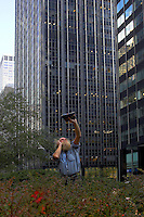 Among all the glitz and color of New York city's skyscrapers a homeless person prays out loud while raising his bible towards the sky...