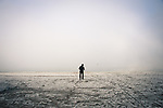 Silhouetted man in a hat on an empty beach in the winter fog.