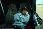 Perez, 19, tries to keep warm and awake on a bus headed to Mexico. Perez was going to Chiapas from Florida were he was a picker which he called hard work and boring.