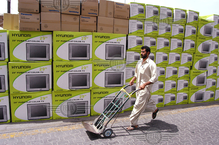 A porter wheels his trolly along a stack of boxed televisons in Dubai Creek, a free trade zone and the hub for the Indian Ocean Dhow trade.