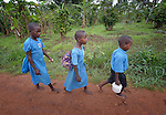 Children walk to school in the morning in Lukaya, Uganda, where the Good Samaritan Women's Project has helped rural women improve their financial literacy, thus improving the quality of life for the women, many of whom are widows who also care for children who lost their parents to AIDS. The program was funded by the Call to Prayer and Self-Denial of United Methodist Women. These children are part of an extended family, where a widow with three children has adopted the four children of her sister who died.