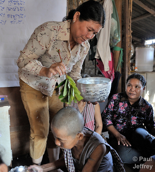 Morn Nen, 48, blesses other members of her self-help group with water in the Phnom Penh neighborhood of Sen Rikreay. Many people in this community are infected or affected by HIV and AIDS, and Buddhist monks and other religious meet with them regularly to mediate and discuss their challenges.