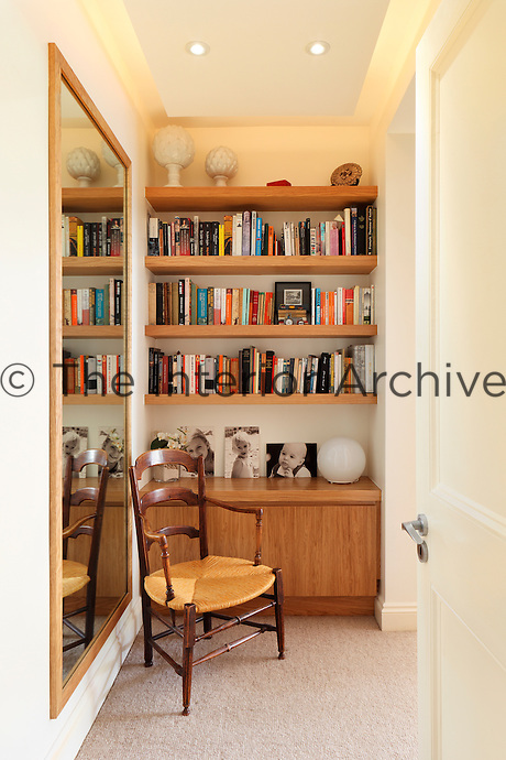 An antique chair is placed in front of a built in cupboard with book shelves above. A full length mirror on the adjacent wall gives a sense of space and a suspended ceiling conceals soft lighting.