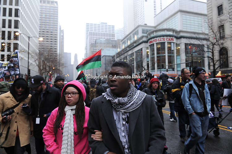 "Protesters take to Michigan Avenue, Chicago's ""Magnificent Mile"" and longest shopping street, including Ja'Mal Green (at center) to protest three days after the release of a dash cam video documenting the killing of Laquan McDonald by Chicago Police Officer Jason Van Dyke, who has been charged with his murder, on Black Friday, the busiest shopping day of the year, in Chicago, Illinois on November 27, 2015.  Van Dyke fired 16 shots at McDonald and fired 13 of those shots after McDonald was on the ground and only stopped after his colleague told him to stand down; a journalist for outlet DNA Info sued the City of Chicago for release of the dash cam video, which the city released only after ordered to do so by a judge last week."