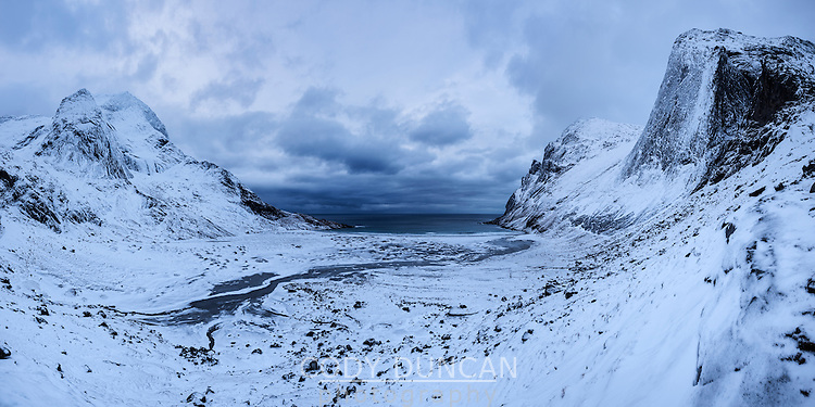 Stormy winter skies over snow covered Bunes beach, Moskenesøy, Lofoten Islands, Norway