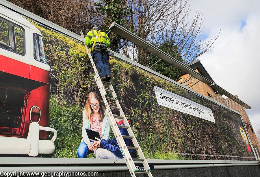 Man standing on ladder billboard for 'diesel in petrol engine' placed on advertising sign, city of Dublin, Ireland, Irish Republic Ireland