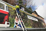 Man standing on ladder billboard for 'diesel in petrol engine' placed on advertising sign, city of Dublin, Ireland, Irish Republic Ireland