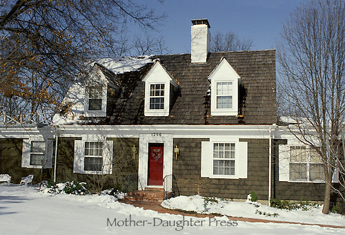 Traditional wooden Cape cod style house with red door in winter snow. Winter series