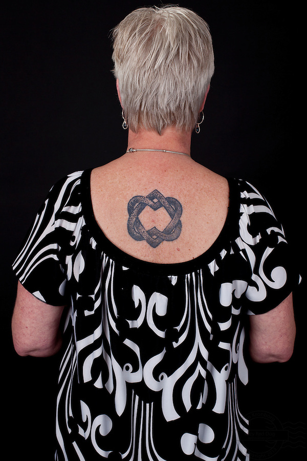 Danish woman with at viking style tattoo on her back. Two hearts interlaced. The tattoo is by Erik Reime from Kunsten på Kroppen.
