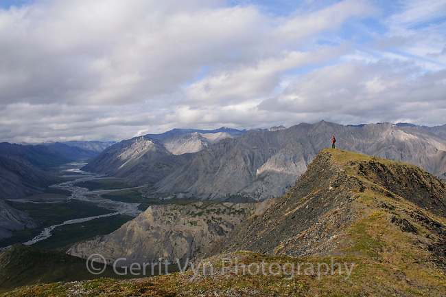 Brooks Range hiker abovethe Canning River valley. Arctic National Wildlife Refuge, Alaska. June.