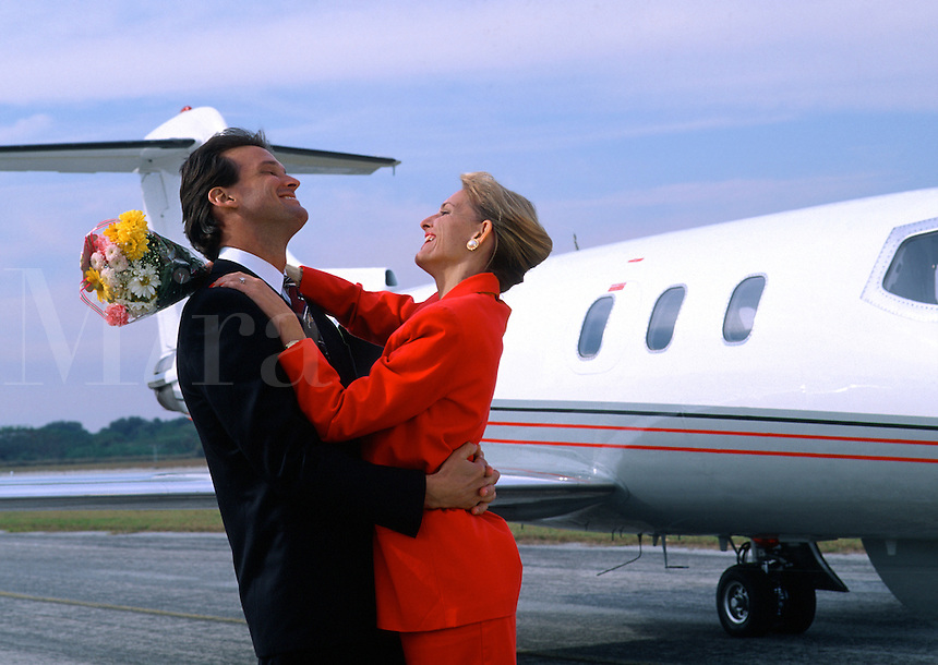 A smiling woman with flowers embraces a businessman with an executive jet in the background.