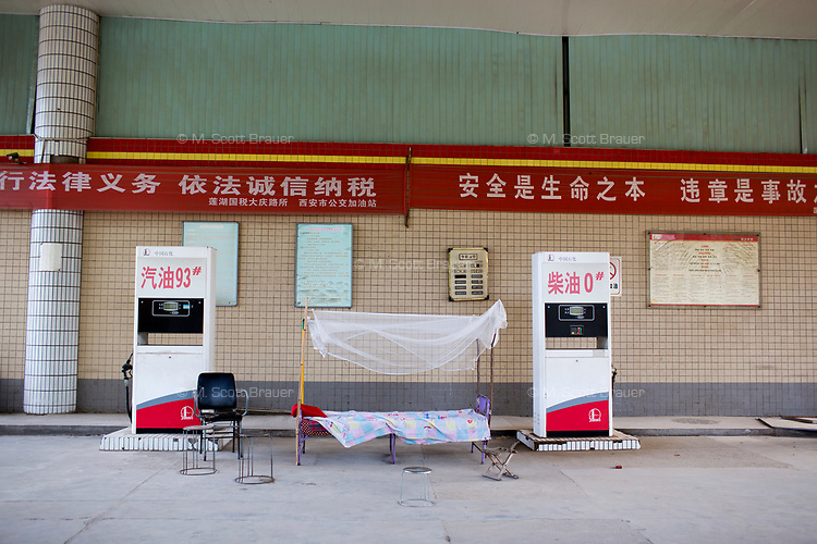 A bed is seen between gas pumps at a gas station in Xian, Shaanxi, China.