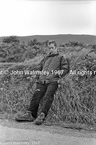 "John Walmsley, then a photography student at Guildford School of Art, on a hitching and camping trip around Southern Ireland, on the road near Dunquin (in Gaelic, Dún Chaoin, meaning ""Caon's stronghold""), on the tip of the Dingle Peninsula, County Kerry, Ireland.  1971."