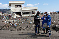 British Journalist, Tom Parry interviewing tsunami survivors in front of a ruined building in Otsuchi in Iwate, Japan. March 17th 2011