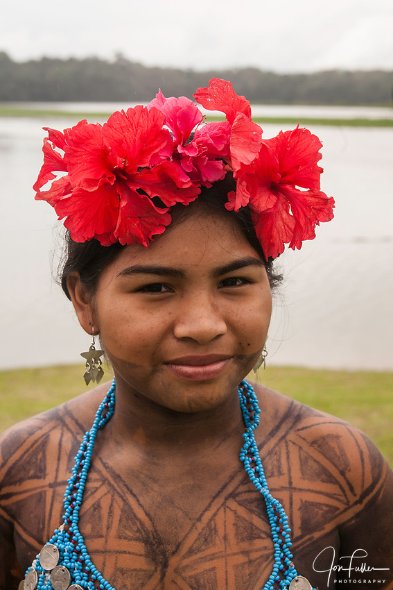 An indigenous Embera woman dressed up for visitors in her village on Lake Alejuela in Panama.  Her body is painted with the juice of the jagua berry to make a temporary tattoo.  It takes about two weeks to wear off.  The women's tops are beaded and often decorated with silver coins. Chagres National Park