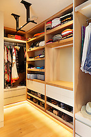 A walk-in wardrobe come dressng room with built in shelving and cupboard space.