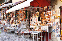 The busy old market bazaar street Kujundziluk with lots of tourist craft and art shops and street merchants. Shops selling a dazzling assortment of souvenirs, paintings, brass and copper pots, jewellers. A man shopkeeper. Historic town of Mostar. Federation Bosne i Hercegovine. Bosnia Herzegovina, Europe.