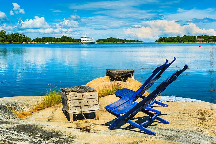 Stolar och sump på en klipphäll och en Waxholmsbåt anländer till Rödlöga Roslagen,