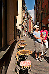 Two kids laugh as they walk in the sunshine, down a cobble stone street in the old town of Stockholm, Sweden