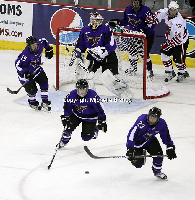 Minnesota State University-Mankato's Kurt Davis (No. 22) and Michael Dorr (No. 23) work to move the puck up ice during the first period. (Photo by Michelle Bishop)