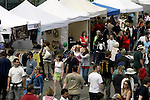 Festival goers past booths before the start of the 21st annual Summer Solstice Parade Saturday, June 20, 2009 in Seattle, Wa.The parade was held Saturday, bringing out painted and naked bicyclists, bands, belly dancers and floats. (Jim Bryant Photo © 2009) .