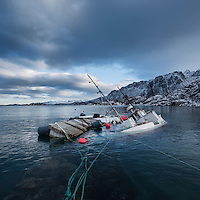 Partially sunken fishing boat floating in harbor, Fiskebøl, Austvågøy, Lofoten Islands, Norway