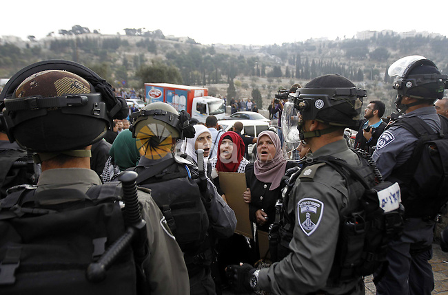 Israeli security forces stand next to Palestinian woman shouting slogans during a rally near the entrance of al-Aqsa mosque compound to protest after authorities restricted access to the esplanade on October 15, 2014 outside Jerusalem's Old City. For the second time in a week, authorities allowed only Palestinians aged over 50 to enter. Four Palestinians were arrested and three police were injured during clashes that followed the protest, police spokeswoman Luba Samri said. Photo by Muammar Awad