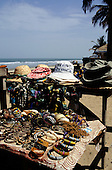 The Gambia. Tourist souvenir bangles, bracelets, necklaces, hats and scarves on a beach stall.