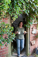 A smiling Jax Fothergill photographed walking from the house into the garden with a cup of tea