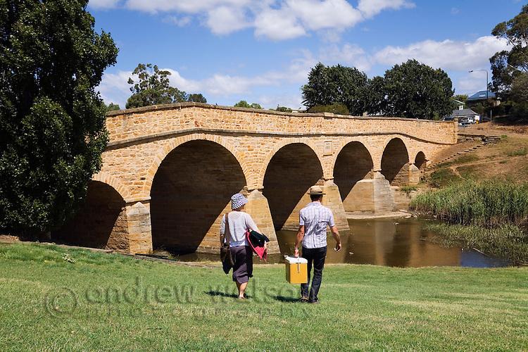 A couple picnic at Richmond Bridge.  Richmond, Tasmania, AUSTRALIA
