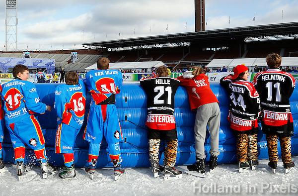 De Coolste Baan van Nederland. Tijdelijke IJsbaan in het Olympisch Stadion in Amsterdam. Jongens kijken naar reen ijshockey wedstrijd
