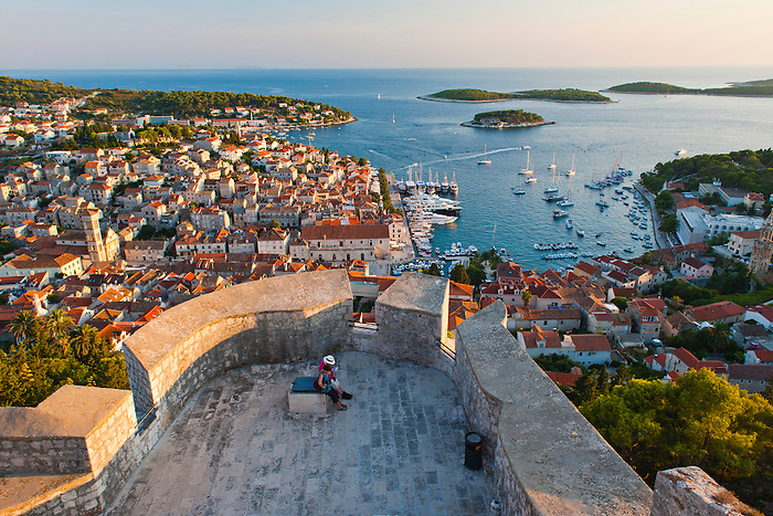Hvar Town and tourists at Hvar Spanish Fortress at sunset, Hvar Island, Croatia, Europe. This photo of Hvar Town at sunset shows Hvar Spanish Fortress, aka Fortica or Hvar Spanish Fort in the foreground. From its position high up on a hill above Hvar Town, it provides the best views over Hvar Town and Island. It is easily worth the walk up to the Spanish Fortress, Fortica, especially at sunset.