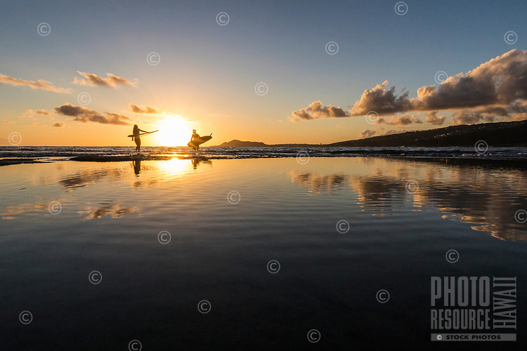 A couple heading out for an evening surf session are reflected in tidal pools near Koko Head, East O'ahu.