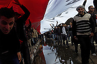 A giant flag of Egypt being carried by a group of young people with the April 6th movement through the streets of Cairo