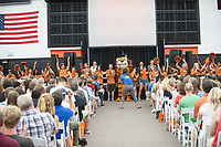 The O-Team welcomes incoming first-years and their families as they walk under the art gate at the entrance to Kemp Stadium during Occidental College Orientation, Aug. 23, 2014.<br /> (Photo by Marc Campos, Occidental College Photographer)