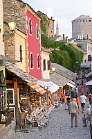 The busy old market bazaar street Kujundziluk with lots of tourist craft and art shops and street merchants. Historic town of Mostar. Federation Bosne i Hercegovine. Bosnia Herzegovina, Europe.