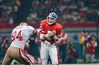 NEW ORLEANS, LA - Quarterback John Elway of the Denver Broncos is hit by San Francisco 49ers defender Charles Haley during Super Bowl XXIV at the Superdome in New Orleans, Louisiana in January of 1990. Photo by Brad Mangin...