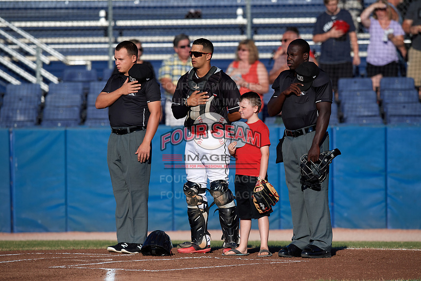 """Batavia Muckdogs catcher Igor Baez (29) stands with umpires Jordan Sandberg (left), James Jean (right), and a """"Star of the Game"""" kid for the national anthem before a game against the State College Spikes on July 7, 2018 at Dwyer Stadium in Batavia, New York.  State College defeated Batavia 7-4.  (Mike Janes/Four Seam Images)"""