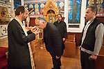 Father Budimir Andjelic venerates the cross inside St. Sava Church as Dan Stojanovich and Miloje Milinkovic await at St. Sava Church, Jackson