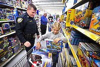 STAFF PHOTO BEN GOFF  @NWABenGoff -- 12/09/14 Jayden Cruse, 8, picks out presents for himself and his two younger sisters while shopping with Bentonville Police Sgt. Ray Shastid during the Bentonville Fraternal Order of Police's annual Shop With a Cop event at the Walmart Supercenter in Bentonville on Tuesday Dec. 9, 2014. Fifty elementary school children from Bentonville schools went shopping with a police officer to find gifts for themselves and their family.