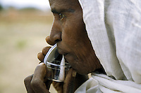 Eritrea. Debub province. Addi Bezhamis. Small village. Health station. Behavioural Change Communication (BCC). Suspected tuberculosis (TB) case. A black old woman spits sputum in a plastic sputum cup. The Global Fund through the eritrean Ministry of Health supports the programm with a Tuberculosis grant (financial aid). © 2006 Didier Ruef