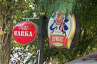 Warka and Zywiec beer signs at a bar near the city park.  Rawa Mazowiecka  Central Poland