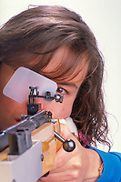 Female Biathlete taking aim with her rifle, close up portrait, gun, arms, sport, hunting, athlete, woman, weapon. Corrina Birnbaum. Colorado.