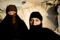 77 year old Shaikha Abdelbaset (left) and her friend 84 year old Hamda Qasem outside a tent in Zaatari Refugee Camp. They both hope that they will be able to return to Syria to be buried in its soil. Approximately two million people have fled the conflict in Syria. At least 130,000 of them live in Zaatari Refugee Camp, although it was designed to house 60,000, and a further 2,000 people arrive each day.