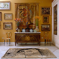 In this living room a collection of 20th century art is displayed on a wall painted dark yellow whilst an antique trunk houses sculptures and plates