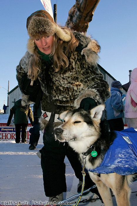 Wednesday March 14, 2007   ----   1985 champion Libby Riddles pets a Mitch Seavey dog shortly after he crossed the finish line in Nome