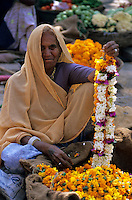 India, Rajasthan, near Udaipur: old local woman selling garlands in market | Indien, Rajasthan, bei Udaipur: alte, einheimische Frau verkauft Blumenkraenze auf dem Markt